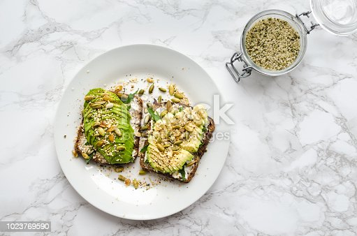 Healthy avocado toasts for breakfast or lunch with rye bread, sliced avocado, arugula, pumpkin, hemp and sesame seeds, salt and pepper. Plant-based diet. Clean eating. Top view. Copy space.