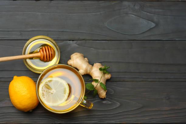 gesunden hintergrund. honig, waben, zitrone, tee, ingwer auf dunklen holztisch. draufsicht mit textfreiraum - heiße zitrone stock-fotos und bilder