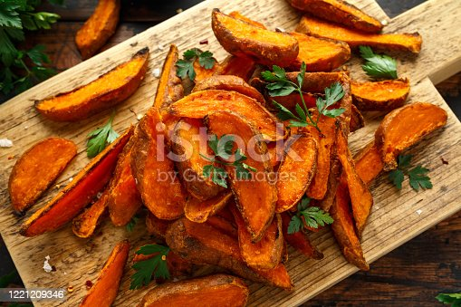 Healthy Baked Orange Sweet Potato wedges with dip sauce, herbs, salt and pepper on wooden board.