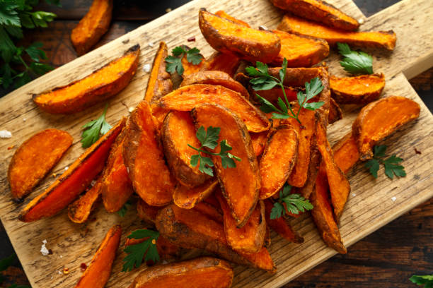 Healthy Baked Orange Sweet Potato wedges with dip sauce, herbs, salt and pepper on wooden board stock photo