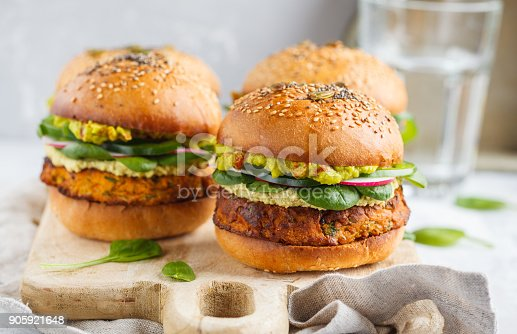 istock Healthy baked sweet potato burger with whole grain bun, guacamole, vegan mayonnaise and vegetables on a wooden board. Vegetarian food concept, light background. 905921648