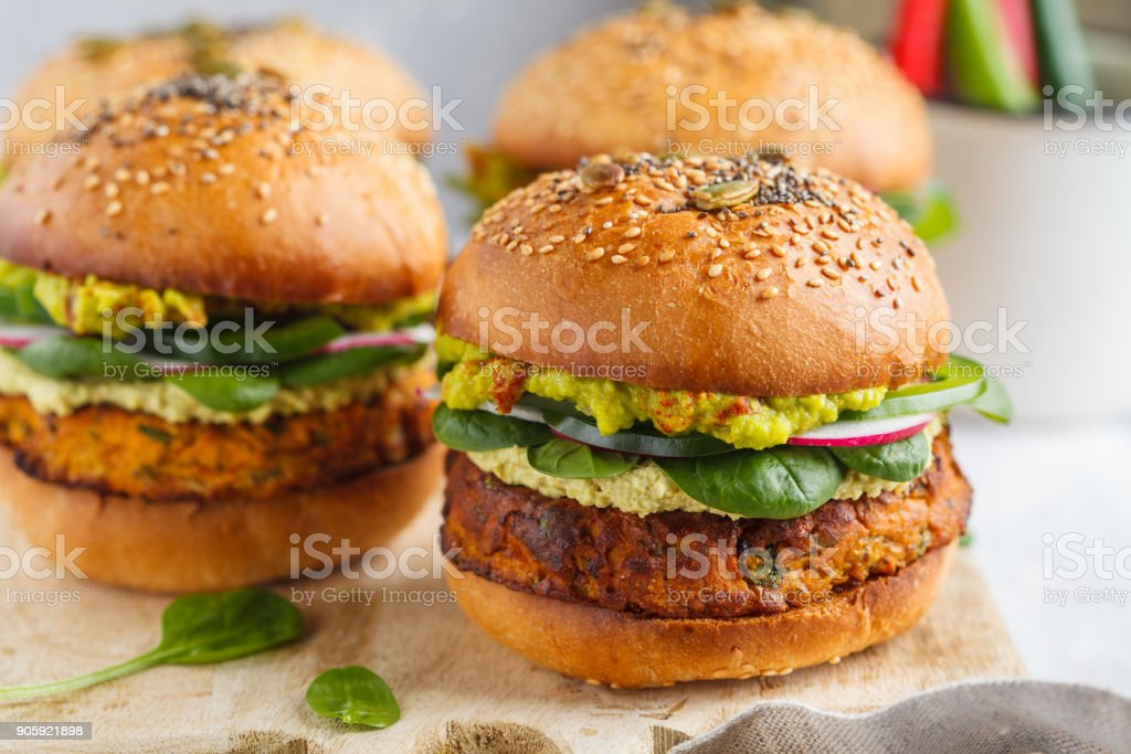 Healthy baked sweet potato burger with whole grain bun, guacamole, vegan mayonnaise and vegetables on a wooden board. Vegetarian food concept, light background. stock photo