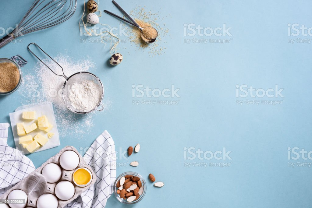 Healthy baking ingredients - flour, almond nuts, butter, eggs, biscuits over a blue table.