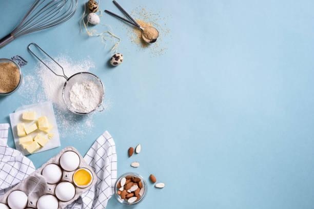 gesunde backzutaten - mehl, mandeln, butter, eiern, keksen über einen blauen tisch. - backrahmen stock-fotos und bilder