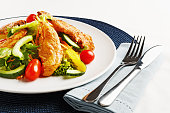 """""""Appetizing shot of a balanced light, low carbohydrate meal consisting of crisply-grilled Tandoori chicken with a salad of cherry tomatoes, cucumber, carrot, sweet yellow bell peppers and lettuce."""""""