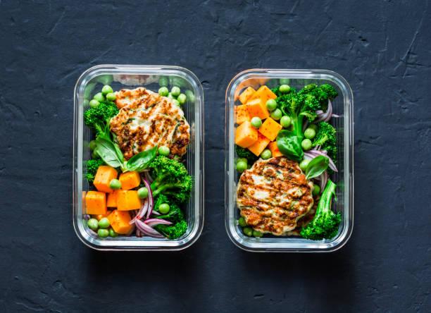 hälsosam balanserad lunchbox. grillad kyckling zucchini hamburgare med broccoli, pumpa, gröna ärtor sallad på en mörk bakgrund, ovanifrån. office mat lunch hälsosam livsstilskoncept - lunchlåda bildbanksfoton och bilder