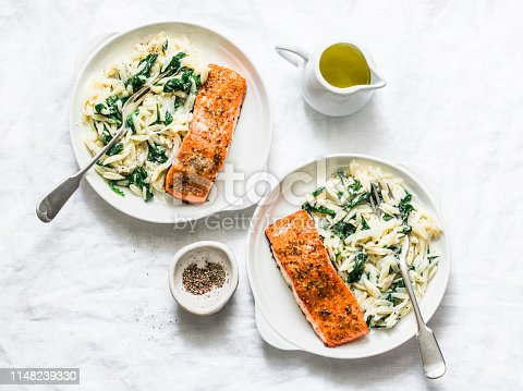 Healthy balanced lunch - creamy spinach orzotto and baked salmon on a light background, top view