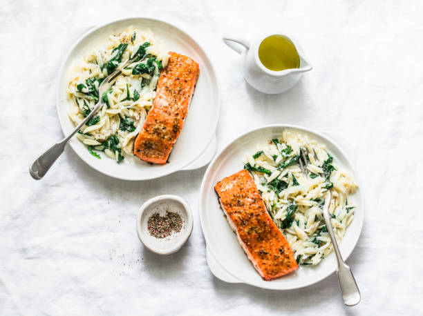 healthy balanced lunch - creamy spinach orzotto and baked salmon on a light background, top view - mediterranean food imagens e fotografias de stock