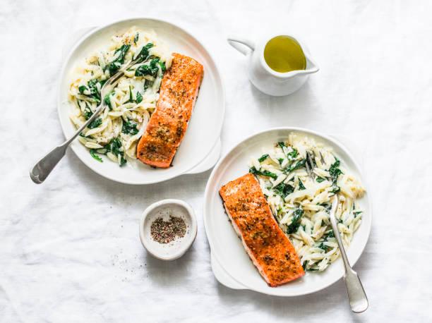 Gesundes, ausgewogenes Mittagessen-cremiger Spinat und gebackener Lachs auf hellem Hintergrund, Top-Ansicht – Foto