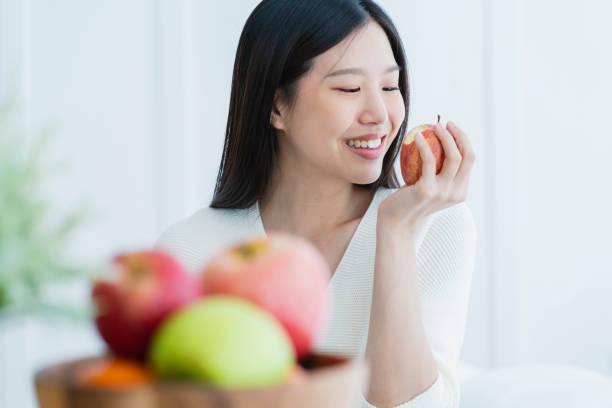 Gesunde schöne schöne lange schwarze Haare Frau Glück Glück Lächeln von Hand halten roten Apfel mit dem Vordergrund der Obstschale weißen Raum Innenausbau – Foto