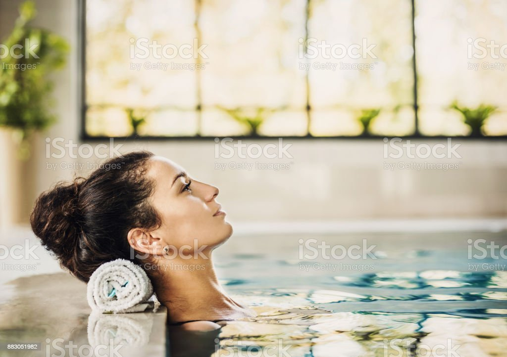 Healthy beautiful woman relaxing at spa swimming pool stock photo