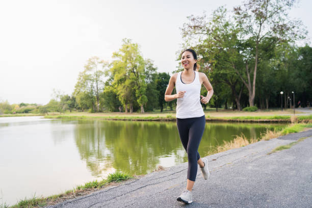 Gesunde schöne junge asiatische Läuferin in Sportkleidung Laufen und Joggen auf dem Bürgersteig in der Nähe des Sees am Park am Morgen. Lifestyle-Fitness und aktive Frauen trainieren im Stadtkonzept. – Foto