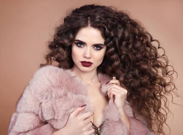 gesunde schönheit haare. glamour portrait schöne brünette frau modell mit marsala matte lippen make-up und lange lockige frisur in luxus pelz mantel isoliert auf beige hintergrund - vampir schminken frau stock-fotos und bilder