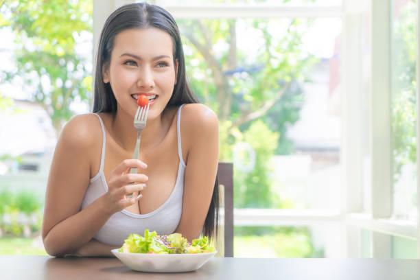 Belleza saludable joven asiática mujer está comiendo ensalada verde para el concepto de comida estilo de vida saludable con tenedor y tomates que van en su boca - foto de stock