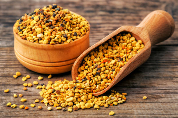 healthy bee pollen on wooden background stock photo