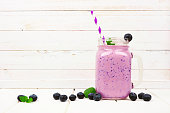 istock Healthy blueberry smoothie in a mason jar with scattered fruit against white wood 1136050199