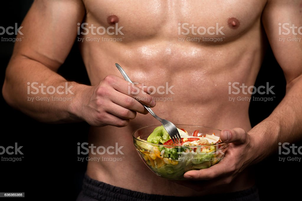 healthy body building man holding a fresh salad bowl stock photo