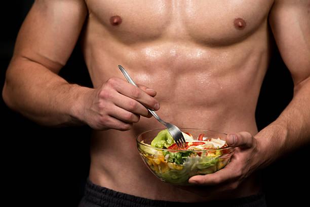 healthy body building man holding a fresh salad bowl stock photo