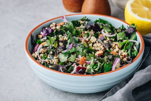 Healthy bowl kale and quinoa salad with cranberry, red onions and almonds Healthy bowl kale and quinoa salad with dry cranberries, red onions and almonds kale stock pictures, royalty-free photos & images