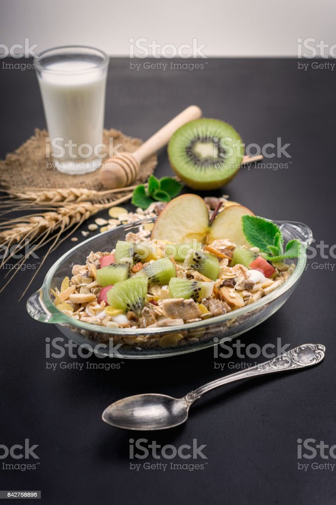 Healthy bowl of muesli, fruit, nuts and milk for a nutritious breakfast on black background. stock photo