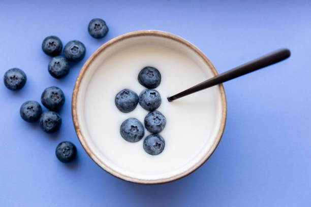 Healthy bowl of yogurt with blueberries and spoon on blue/purple background stock photo