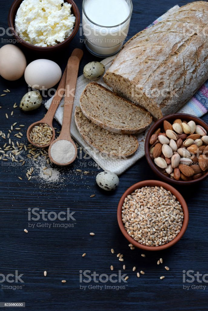 Healthy breakfast. Balanced diet, cooking, dieting, culinary and food concept. Different foodstuffs - whole grain bread, cereal,  cottage cheese, milk, egg, nut, yeast. Top view. Flat lay. stock photo