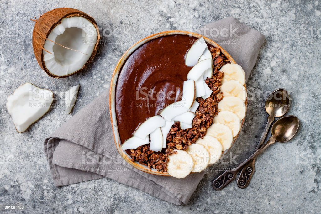 Healthy breakfast bowl. Chocolate banana smoothie bowl with coconut flakes, granola, banana slices. Top view, flat lay, overhead stock photo
