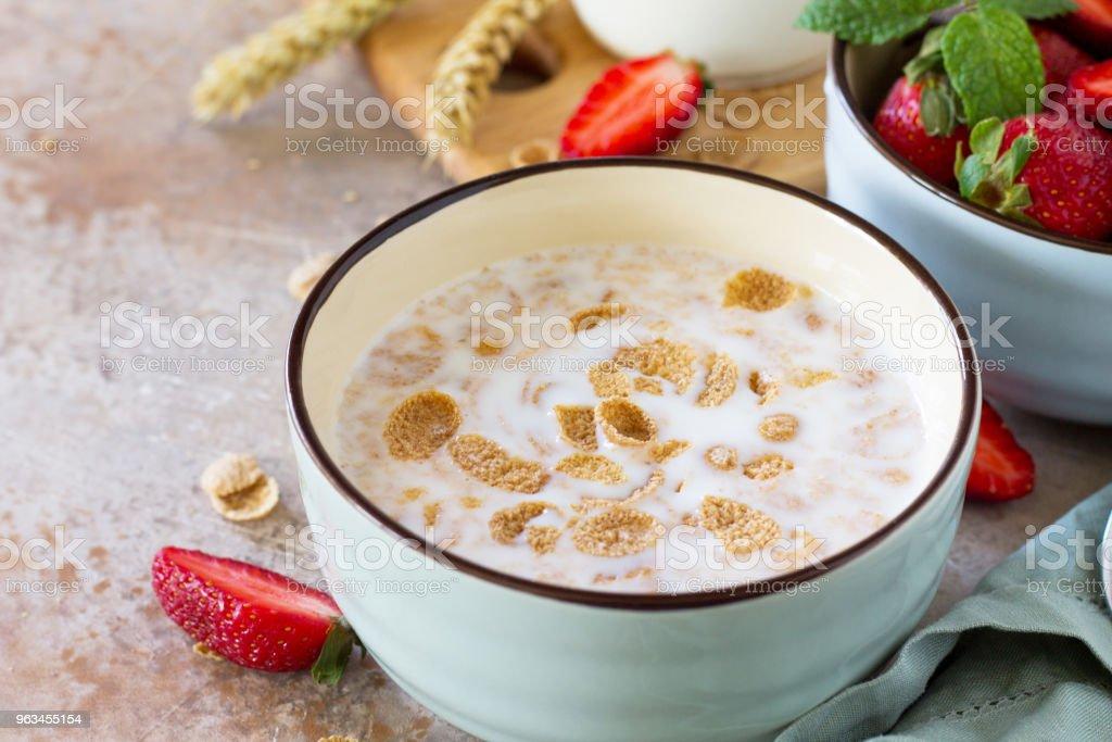 Hälsosam frukost närbild - hela korn flingor, mjölk och färska jordgubbar på sten eller skiffer bakgrund. Begreppet hälsa. - Royaltyfri Bildbakgrund Bildbanksbilder