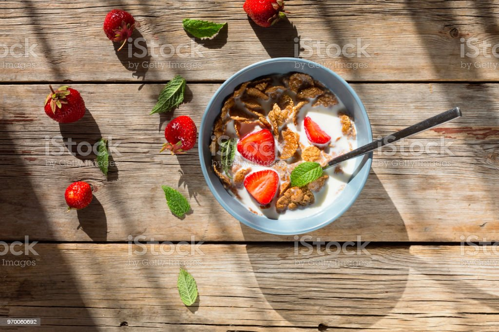 healthy breakfast, Cornflakes, cereal, fruit, milk, eating, morning, nutrition, gray bowlon, wooden background, top view. copy space stock photo