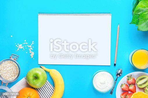 istock Healthy Breakfast Food Oats Orange Juice Green Apple Banana Strawberries Kiwi Yogurt on Blue Tabletop Background. Blank Mock up Notepad for Text. Clean Eating Detox Nutrition Meal Planning Concept 966179136