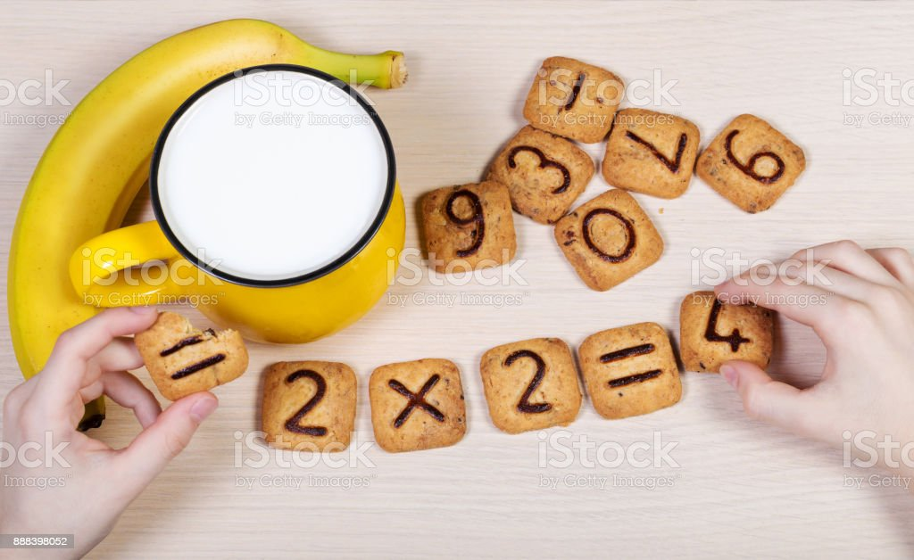 Healthy breakfast for a school children. Milk, banana and funny cookies with numbers. Child's hands doing sums using biscuits. Idea of easy arithmetics during eating. stock photo