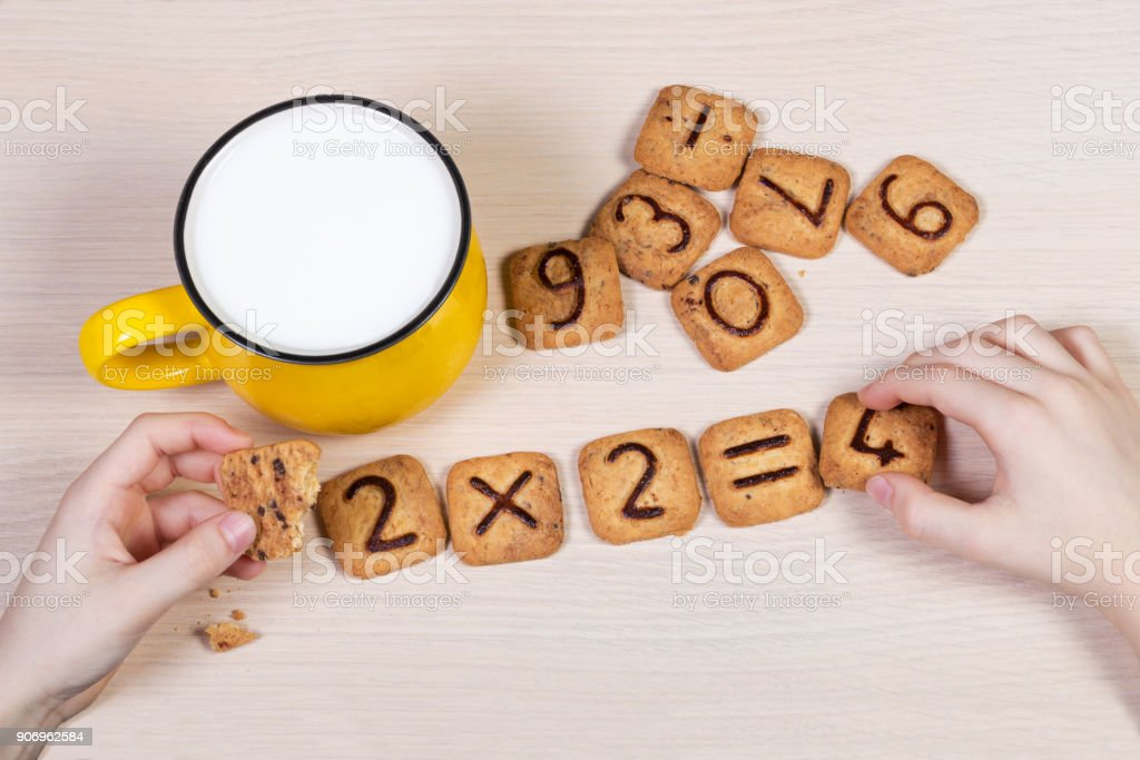 Healthy breakfast for a school children. Milk in bright yellow cup and funny cookies with numbers. Child's hands doing sums using biscuits. Idea of easy arithmetics during eating. stock photo
