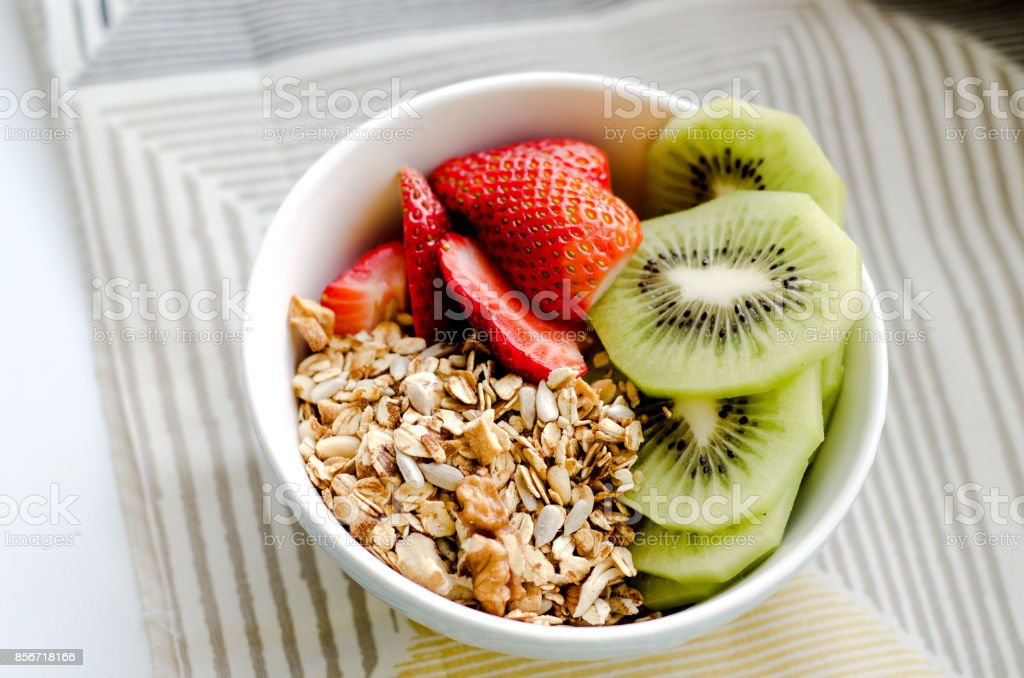 Healthy breakfast fresh granola, muesli in bowl with cereal, nuts, banana fruit, honey with drizzlier, glass of water, bottle, Daffodil flowers. Top view food, Diet, Detox, Clean Eating or Vegetarian stock photo
