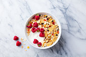Healthy breakfast. Fresh granola, muesli with yogurt and berries on marble background. Top view.