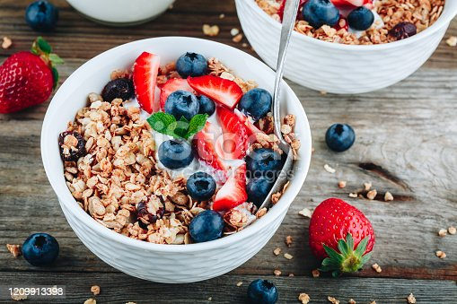 599887760 istock photo Healthy breakfast granola with fresh strawberry and blueberry. 1209913398
