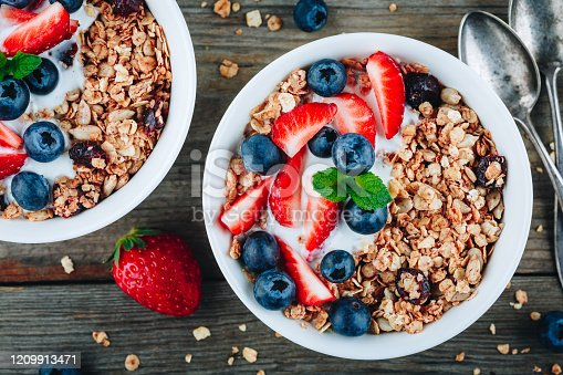 599887760 istock photo Healthy breakfast granola with fresh strawberry and blueberry. 1209913471