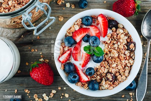 599887760 istock photo Healthy breakfast granola with fresh strawberry and blueberry. 1209913496