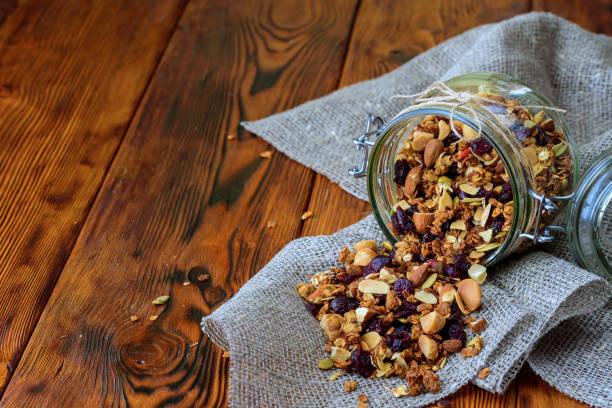 gesundes frühstück hausgemachtem müsli in glas auf hölzernen hintergrund - haferflocken rosinen stock-fotos und bilder