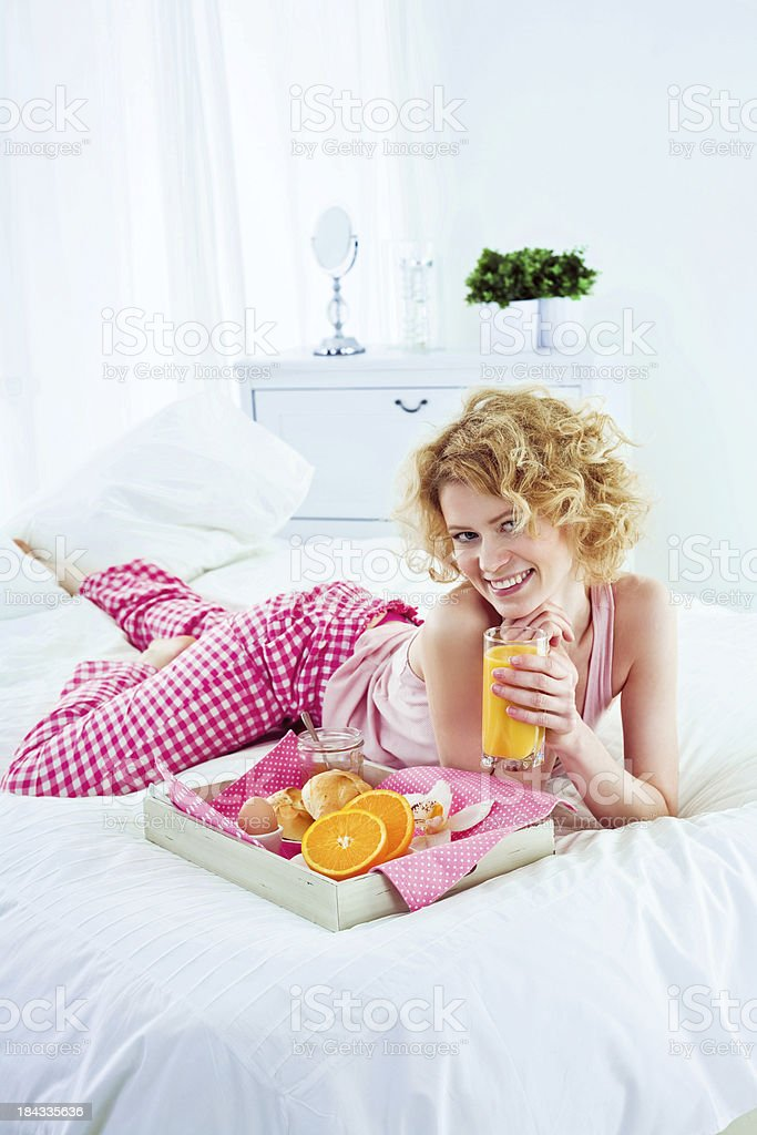 Healthy breakfast in bed Happy young adult woman lying on a bed and going to eat breakfast. Holding a glass of orange juice, looking at camera and smiling. 25-29 Years Stock Photo