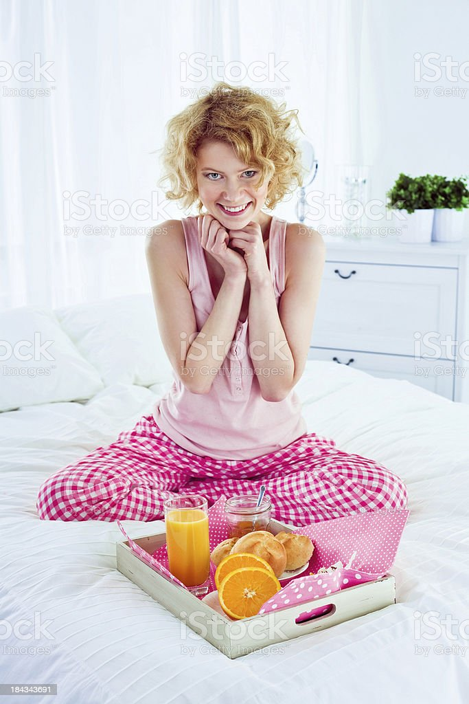 Healthy breakfast in bed Happy young adult woman sitting cross-legged on a bed and going to eat breakfast, looking at camera and smiling. 25-29 Years Stock Photo