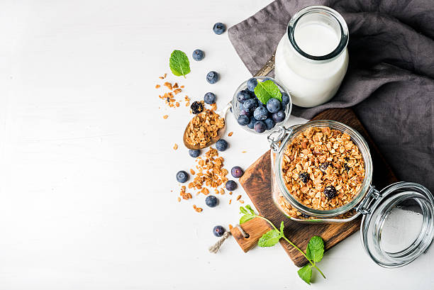 healthy breakfast ingrediens. homemade granola in open glass jar, milk - oats food stock photos and pictures
