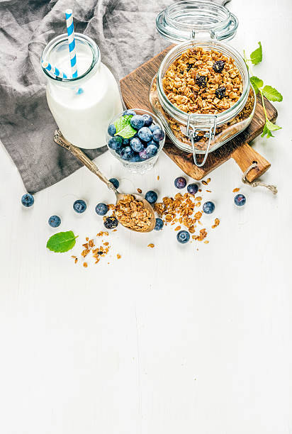 gesundes frühstück ingrediens. hausgemachtem müsli in das glas glas, milch - getreidebrei stock-fotos und bilder