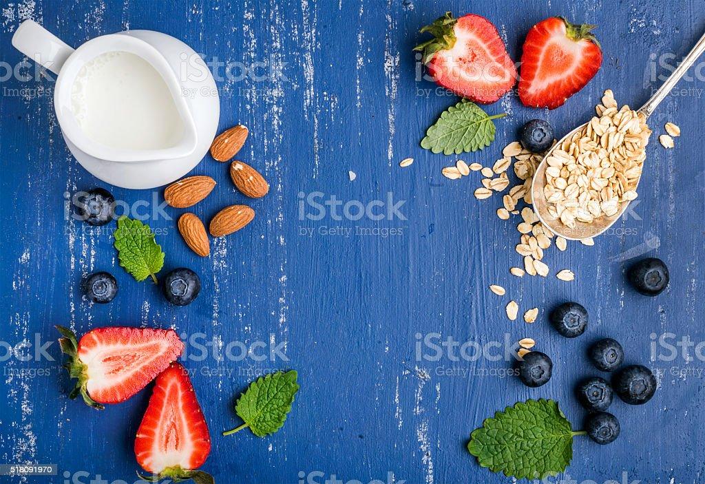 Healthy breakfast ingredients food frame. Oatmeal, milk in creamer, berries stock photo