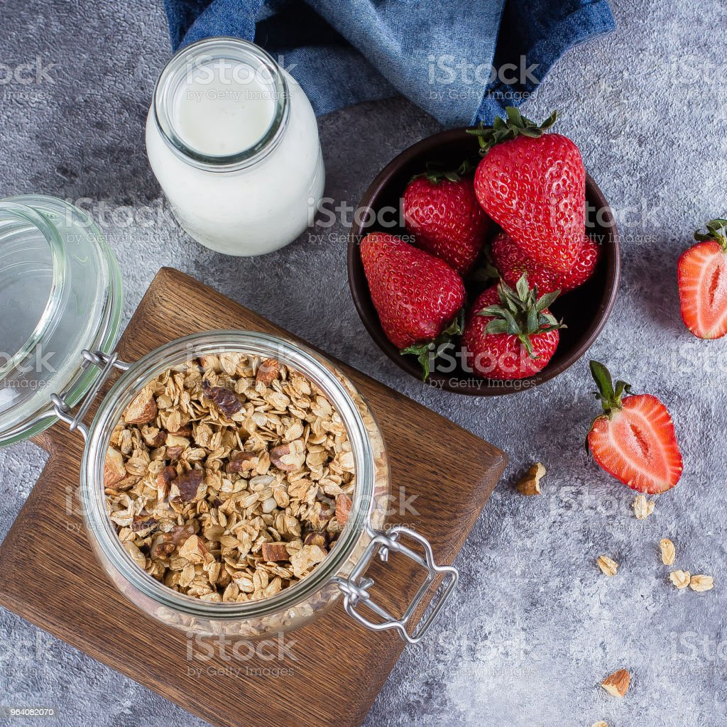 健康的な朝食の食材。オープン ガラス瓶、牛乳やヨーグルトの瓶、灰色のコンクリート背景、上面にいちごの自家製グラノーラ - イチゴのロイヤリティフリーストックフォト