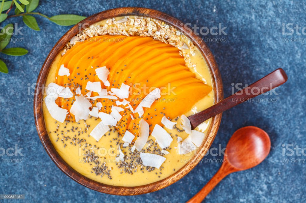 Healthy breakfast mango smoothie bowl with chia seeds, mango slices, coconut slices and oat granola. Banana nice cream. Healthy vegan food concept. stock photo