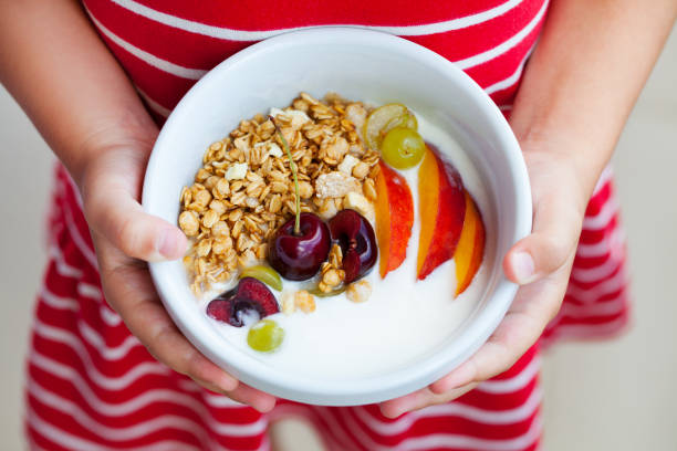 Healthy breakfast. Muesli with yogurt, fruits and berries in little girl's hands. stock photo