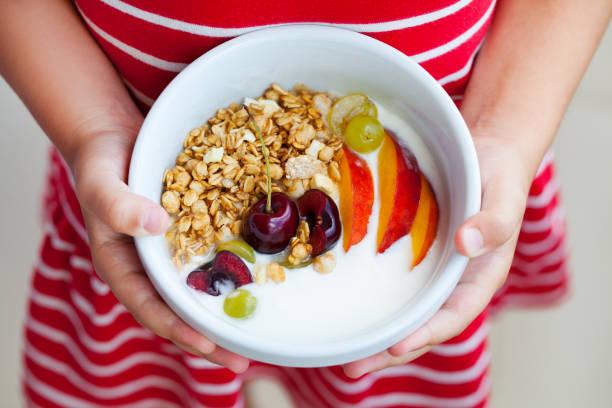 healthy breakfast. muesli with yogurt, fruits and berries in little girl's hands. - pesche bambino foto e immagini stock