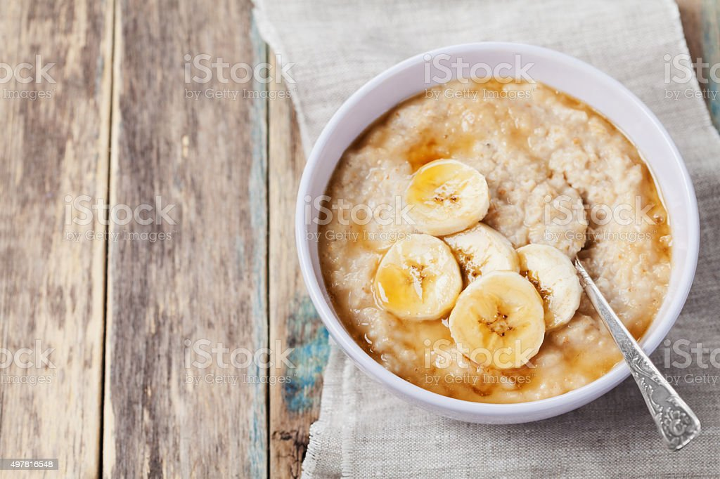 Healthy breakfast, oatmeal porridge with banana with text copy space stock photo