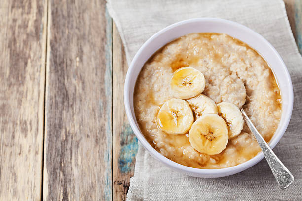 Healthy breakfast, oatmeal porridge with banana with text copy space Bowl of oatmeal porridge with banana and caramel sauce on rustic table, hot and healthy breakfast every day, diet food porridge stock pictures, royalty-free photos & images