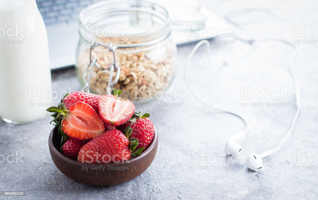 Healthy breakfast on workplace - strawberries, yogurt bottle and granola jar, laptop and headphones on light stone table background. Lifestyle Freelancer Concept. Copy Space - Royalty-free Berry Stock Photo